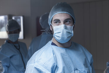 Portrait of surgeon wearing mask with team in background - ZEF007381