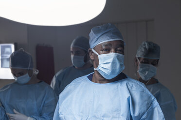 Portrait of surgeon wearing mask with team in background - ZEF007383