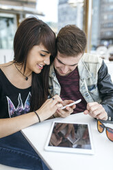 Spain, Gijon, young couple looking at pictures on smartphone - MGOF000398