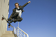 Businessman jumping with his skateboard - ABZF000093