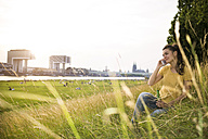 Germany, Cologne, young woman with beer bottle sitting on a meadow near Rhine River telephoning - RIBF000145