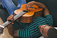 Man sitting on a couch playing guitar - EBSF000833