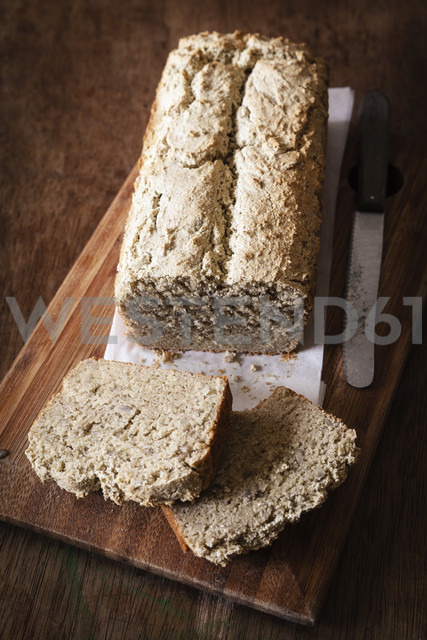 Home-baked wholemeal bread, gluten-free, bread knife on chopping board - EVGF002002