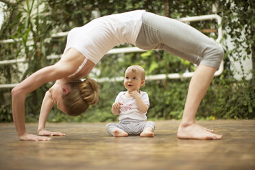 Woman doing yoga exercise while  baby watching her - ABF000630