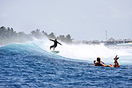 Maledives, South Male Atoll, man surfing while woman lying on her surfboard watching him - FAF000067