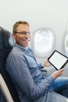 Portrait of smiling man sitting on an airplane holding digital tablet - MFF001981