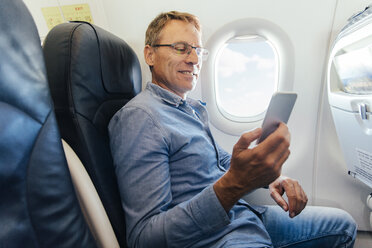 Mature man sitting on an airplane looking at his smartphone - MFF001983