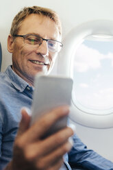 Portrait of smiling man sitting on an airplane looking at his smartphone - MFF001985