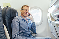 Mature man sitting on an airplane telephoning with his smartphone - MFF001986