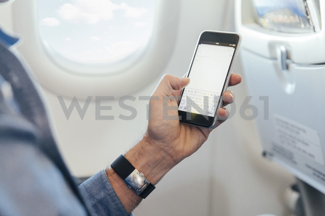 Man sitting on an airplane holding smartphone - MFF001987