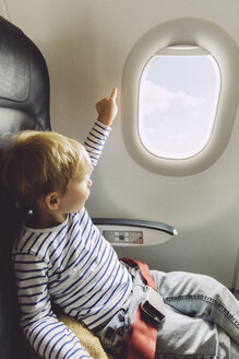 Little boy pointing out of an airplane window - MFF001995