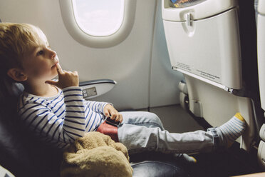 Pensive little boy sitting on an airplane - MFF001991