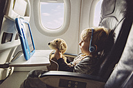 Little boy sitting on an airplane watching something on digital tablet - MFF001994