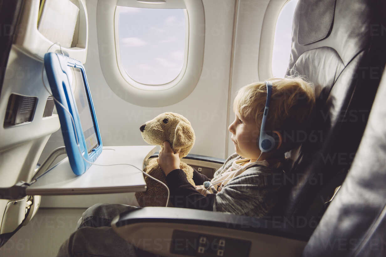 Little boy sitting on an airplane watching something on digital tablet - MFF001994 - Mareen Fischinger/Westend61