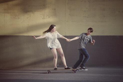 Teenage boy pulling his girlfriend standing on a longboard - MMFF000969