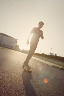 Teenage boy on a longboard at backlight - MMFF000973