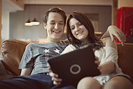 Teenage couple with digital tablet at home - MMFF000976