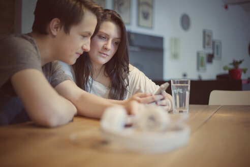 Teenage couple with smartphone at home - MMFF000978