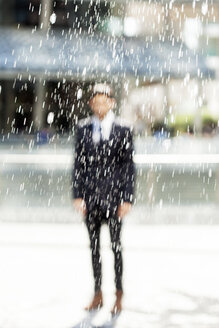 Portrait of blurred businessman standing behind a fountain - PASF000002