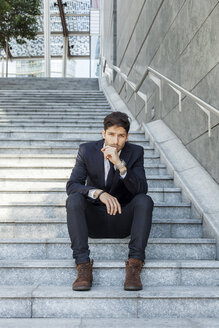 Portrait of young businessman sitting on stairs - PASF000006