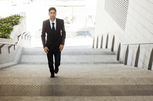 Portrait of young businessman walking up the stairs - PASF000011