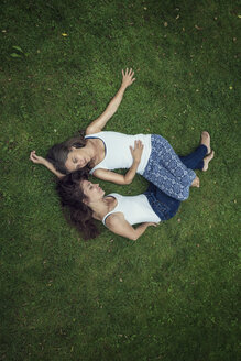 Two sisters lying on a meadow with closed eyes - MW000095
