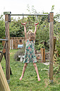 Little girl hanging on gymnastic rings in a garden - MW000101