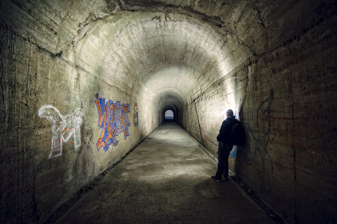 Spain, man leaning on wall of a tunnel - RAE000272