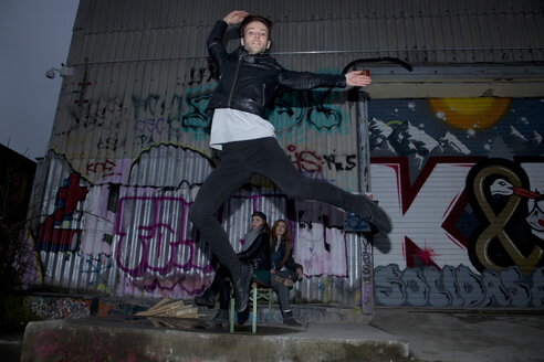 Dancer jumping in front of graffiti - TMF000026
