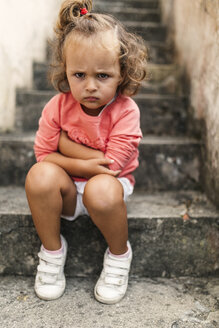 Portrait of little girl sitting on steps pouting mouth - MGOF000403