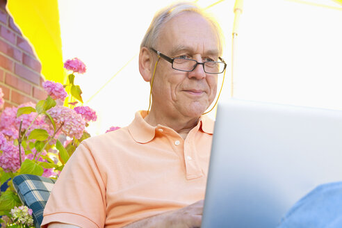 Senior man sitting on a terrace under a sunshade using laptop - MEMF000915