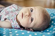 Portrait of baby girl lying on dotted blanket - MFF001955
