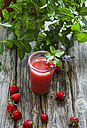 Strawberry smoothie in glass, strawberries and fresh mint on wood - ODF001194