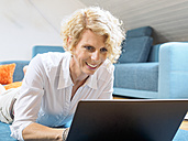 Portrait of smiling blond woman lying on the floor using laptop - LAF001461