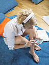 Blond woman with headphones sitting on the floor using smartphone at home - LAF001472