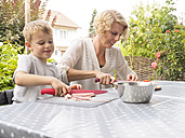 Mother and son preparing food on the terrace - LAF001475