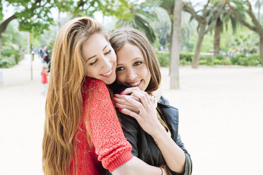 Two female friends hugging in a park - GEMF000301