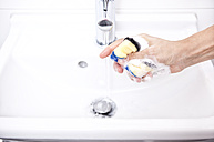 Woman cleaning bathroom sink with sponge - MFRF000341