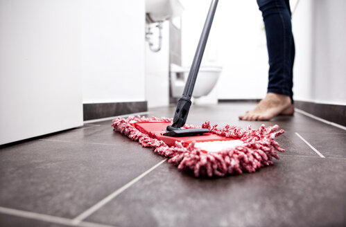 Woman wiping the floor in bathroom - MFRF000344