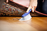 Woman sweeping under the carpet - MFRF000355