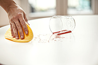 Woman wiping liquid from table from glass fallen down - MFRF000358