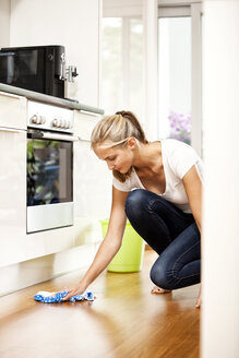 Woman wiping the floor in kitchen - MFRF000364