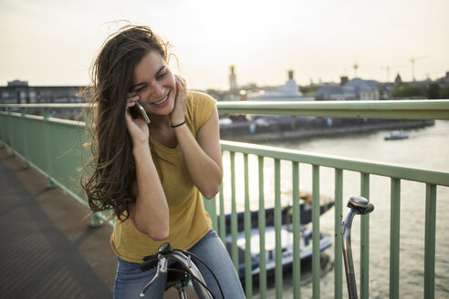 Young woman with bicycle standing on Rhine bridge telephoning with smartphone - RIBF000243