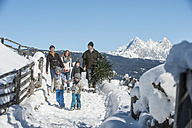 Austria, Altenmarkt-Zauchensee, man with family carrying Christmas tree in winter landscape - HHF005390