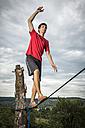 Young man balancing on slackline - STSF000853