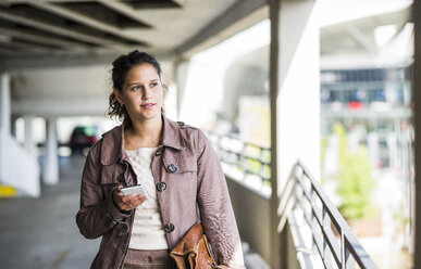 Young woman using smart phone in parking garage - UUF005276