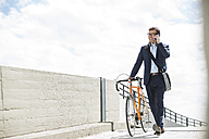 Businessman pushing bike while talking on the phone - UUF005330