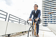 Businessman riding bicycle - UUF005336