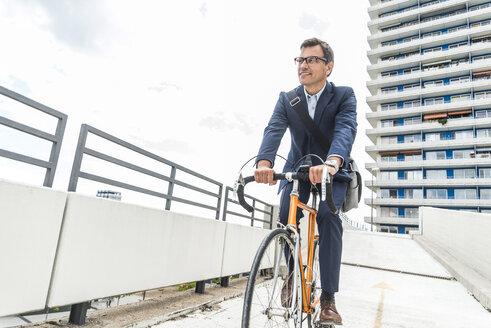 Businessman riding bicycle - UUF005336