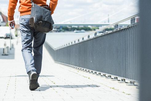 Businessman with shoulder bag walking, rear view - UUF005344